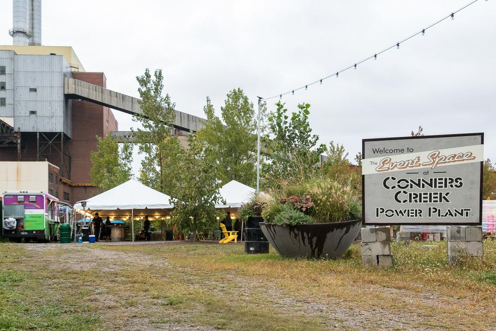 An outdoor event space with lots of greenery at Conner's Creek in Detroit.