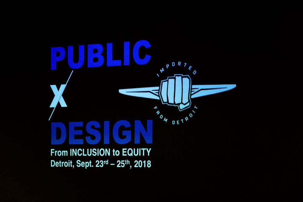 Black and blue image of the Public X Design conference logo on a projector.
