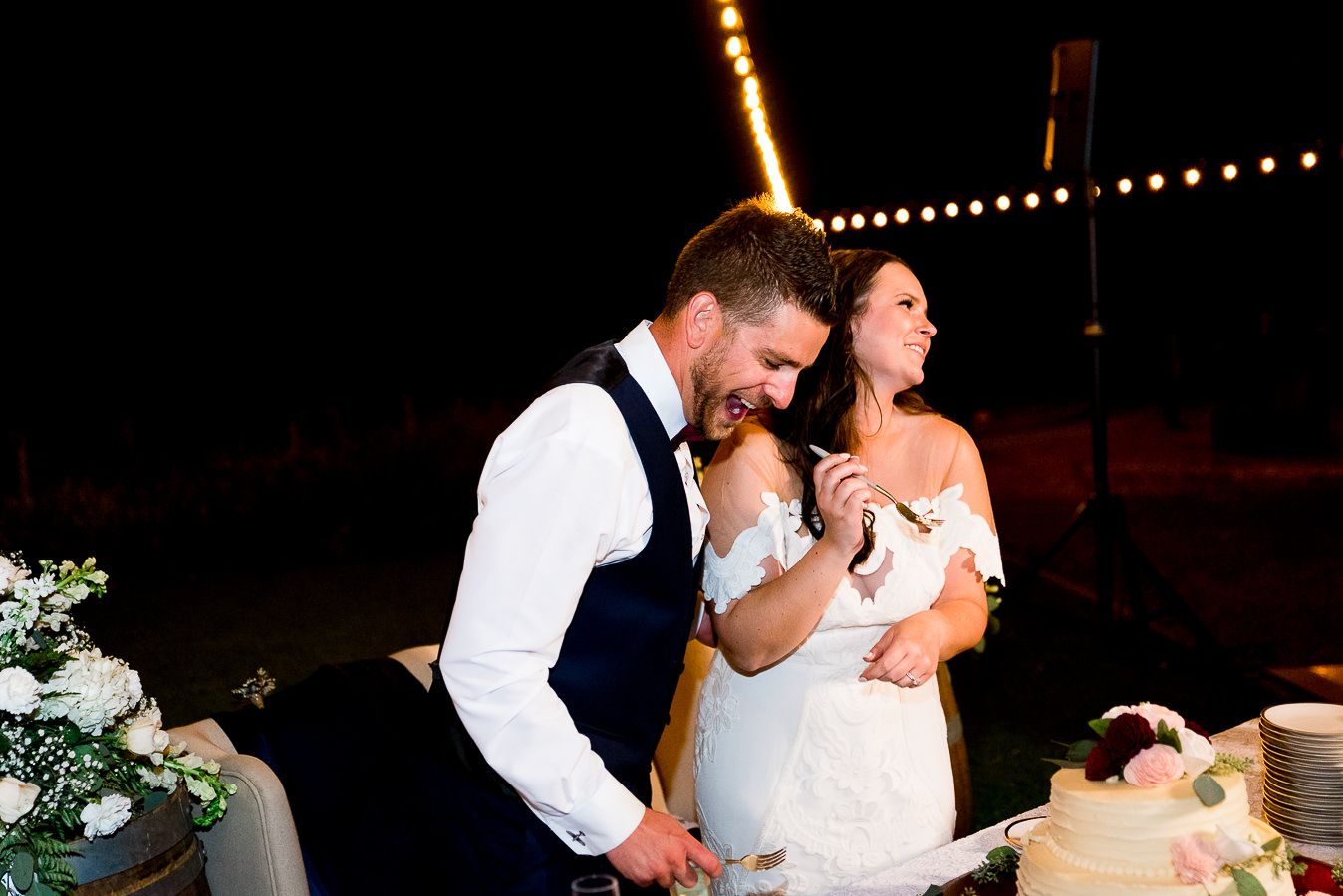 groom laughs as bride feeds him wedding cake at outdoor wedding reception at Pennyroyal Farm