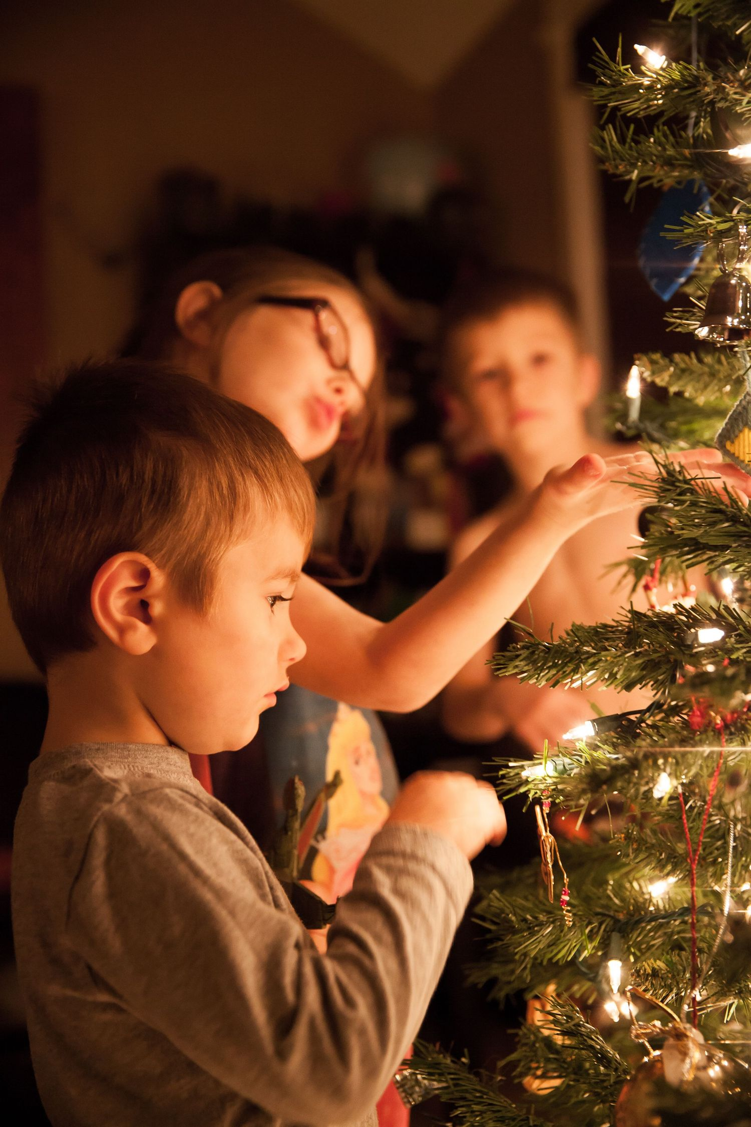 three kids gathered around a Christmas tree