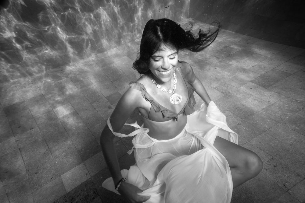 A woman smiling underwater in a white skirt