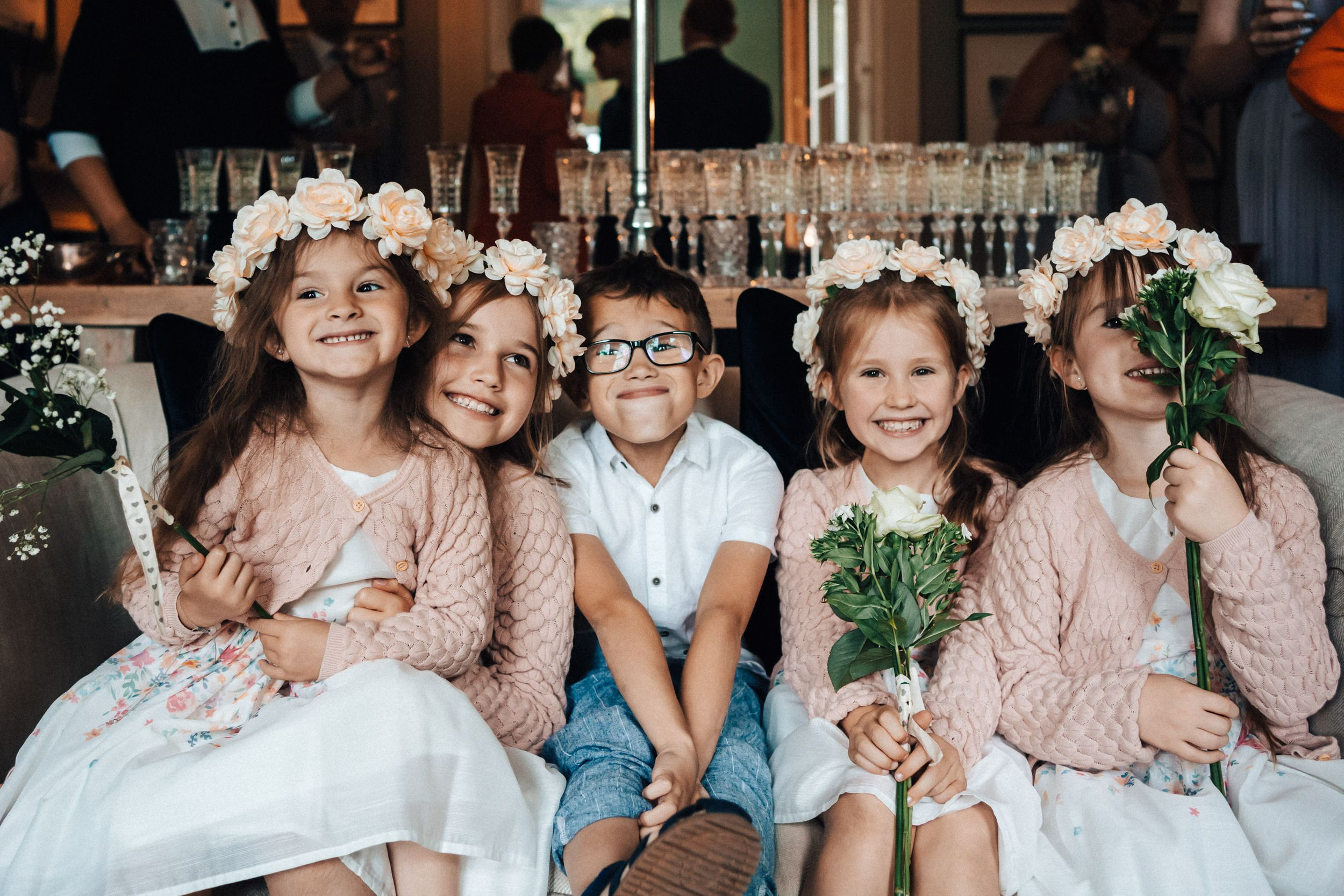 Cheeky photograph of the bridesmaid and pageboy on the sofa pageboys sticking his tongue out