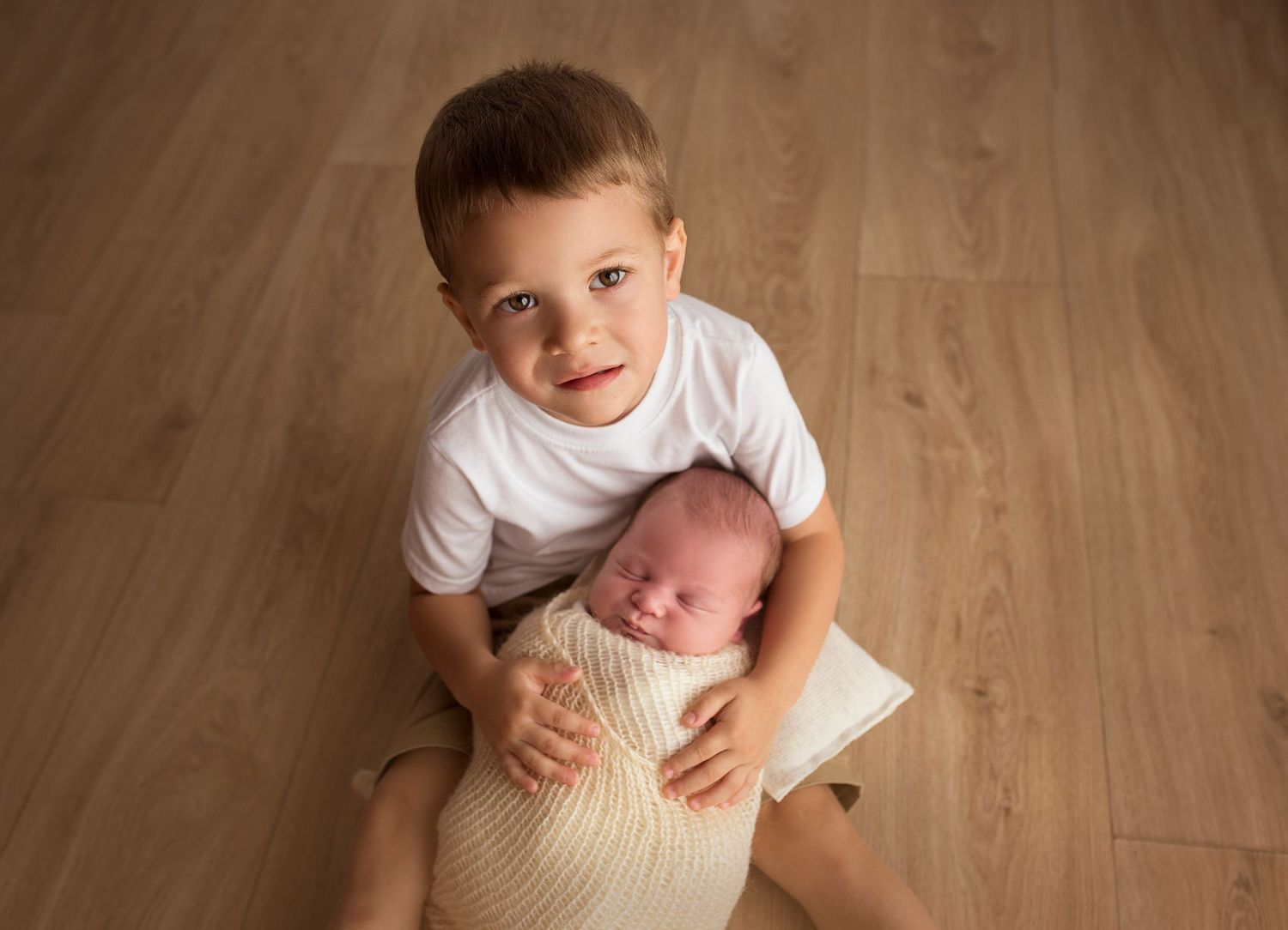 toddler big brother holding newborn