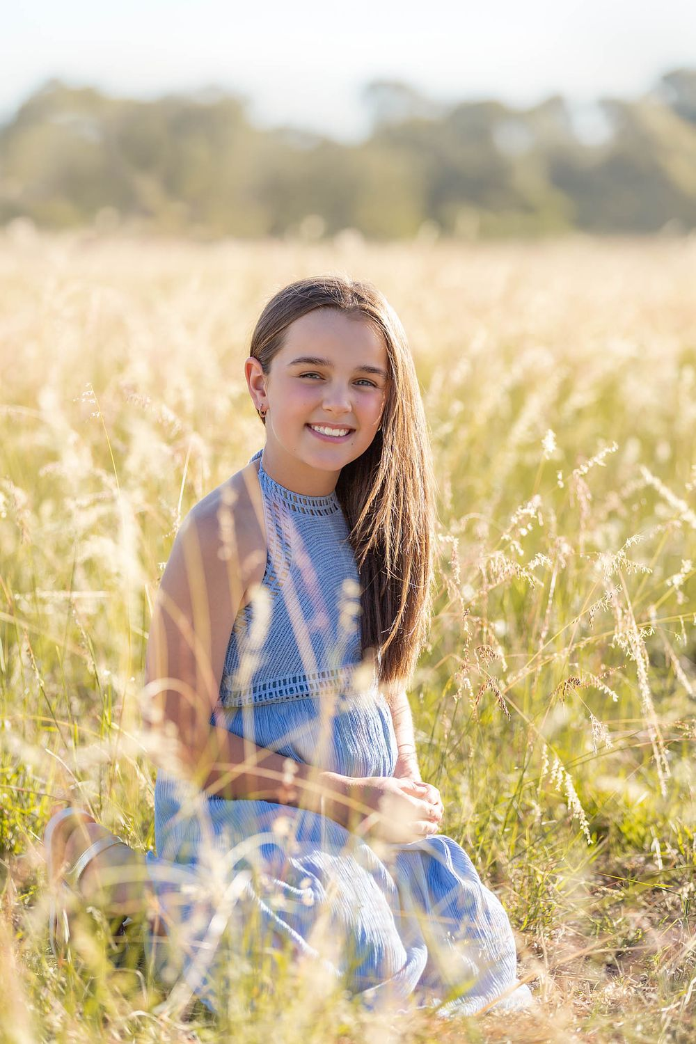 Girl in blue dress sitting in long golden grass