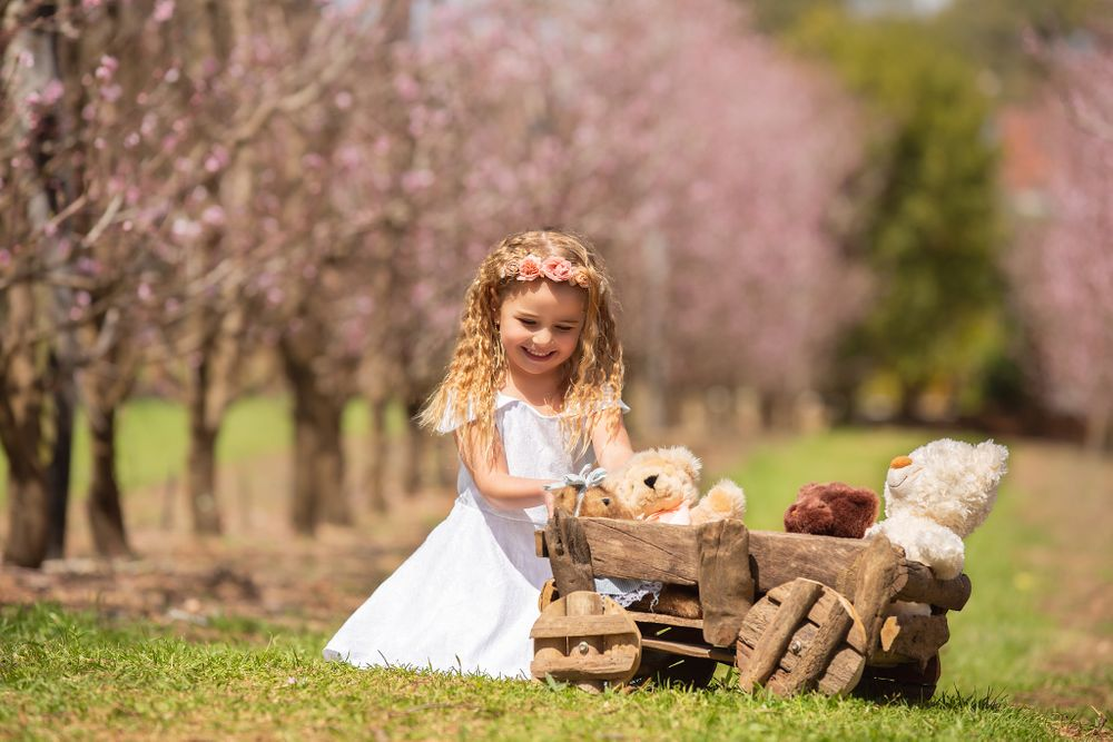 little girl sitting in orchard playing with teddy bear