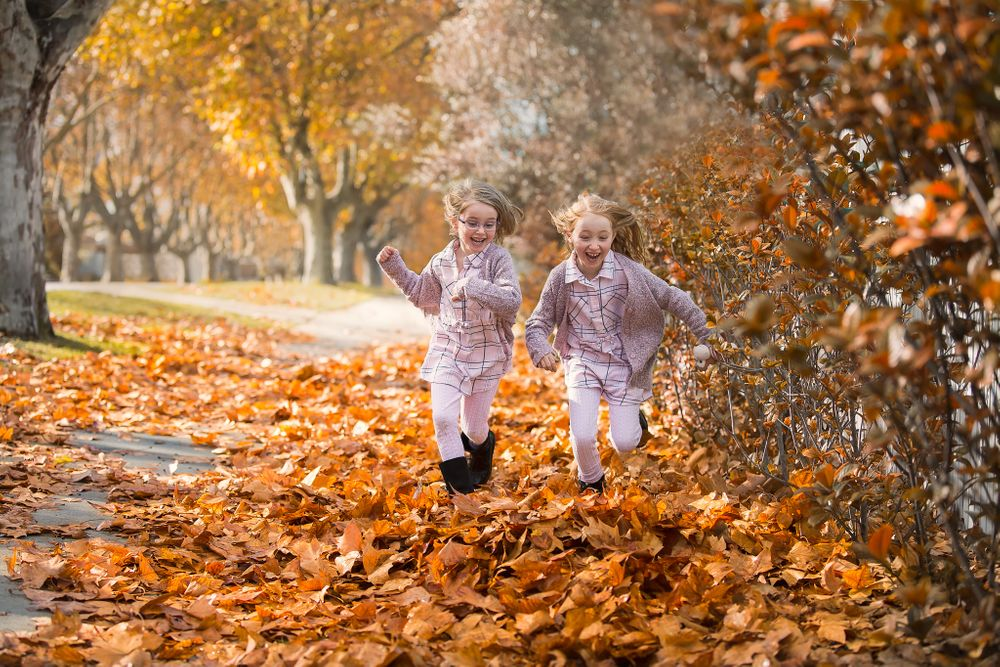 two girls running through autumn leaves laughing having fun