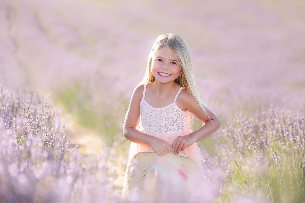 family photography girl in summer dress standing in lavender field