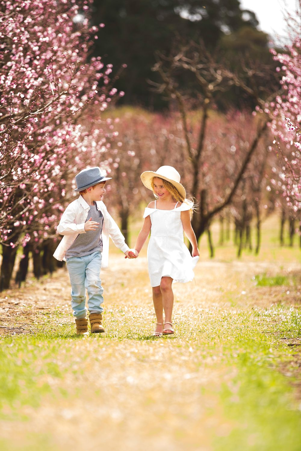 family photography girl and boy holding hands walking in orchard