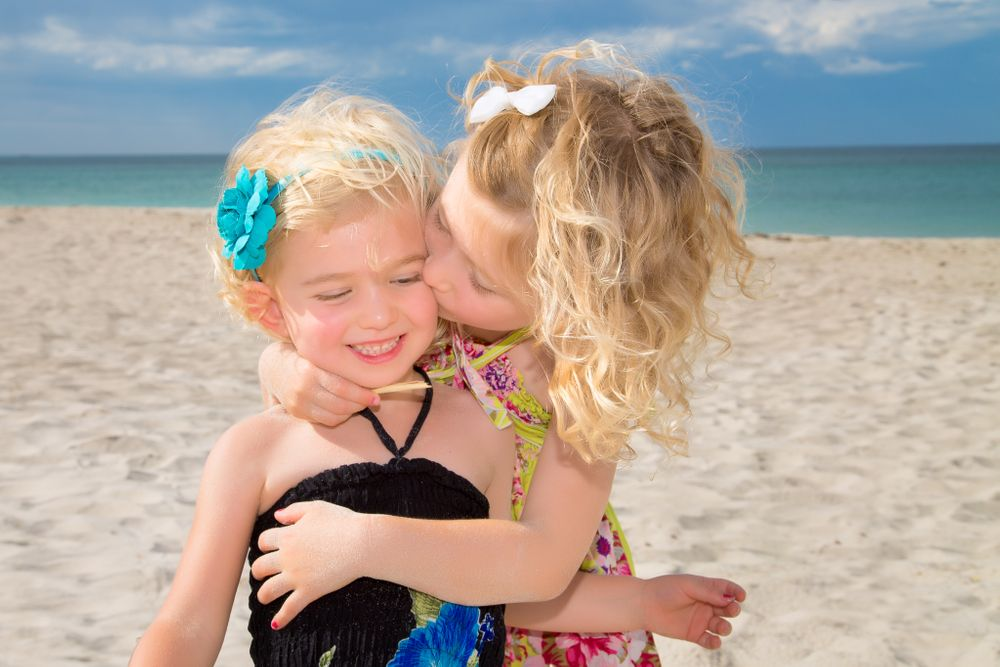 family photography two girls cuddling on beach