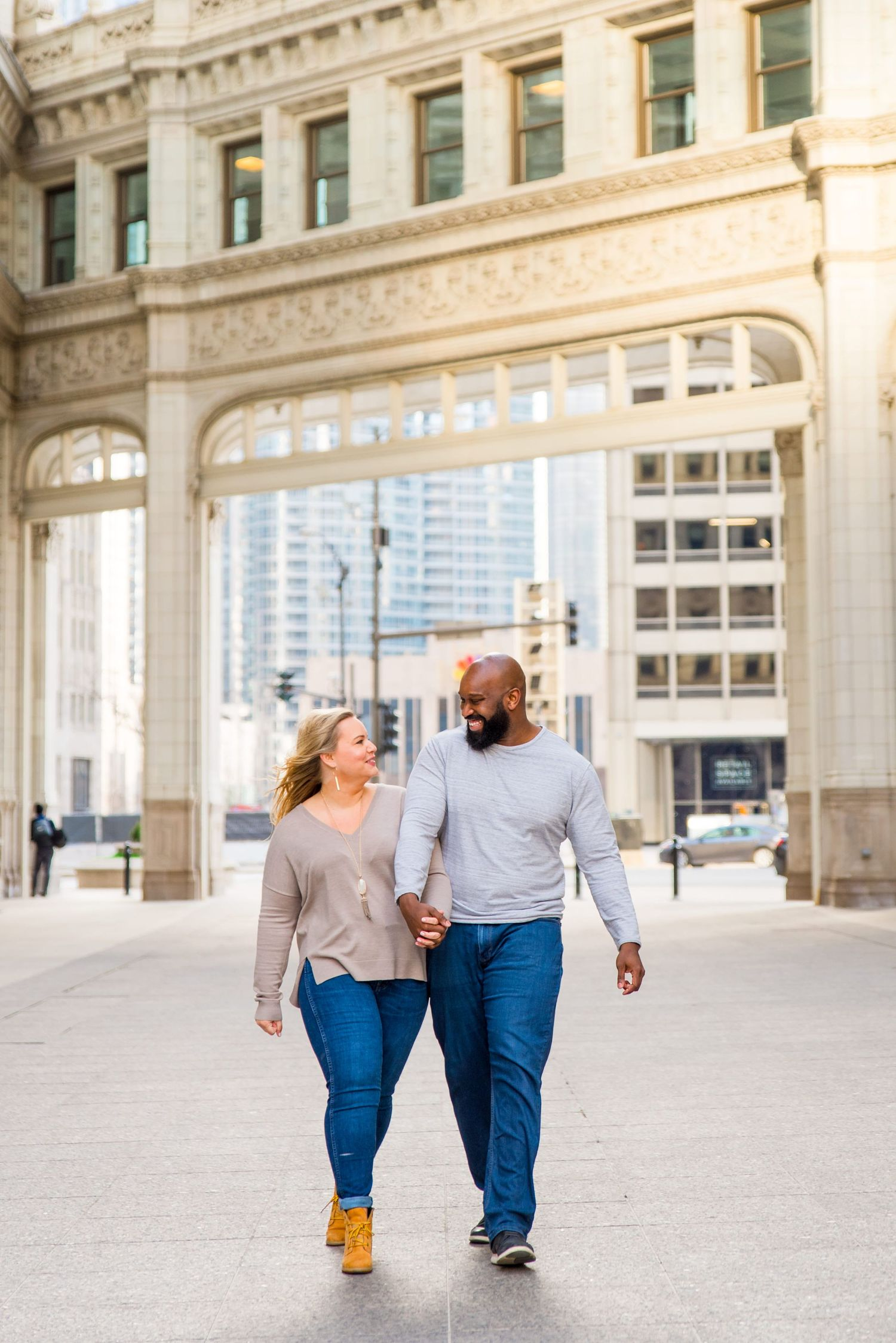 man and woman holding hands laughing at Wrigley Building Chicago engagement photos