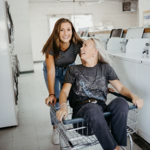 sister-pushing-each-other-in-laundromat-winterset-iowa-raelyn-ramey-photography
