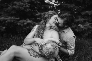 mom-dad-snuggling-while-breastfeeding-outside-iris-aisle-raelyn-ramey-photography