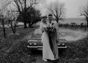 wedding-couple-standing-in-front-of-old-car-vinton-iowa-raelyn-ramey-photography