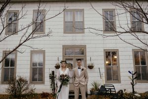 wedding-couple-standing-in-front-of-old-victorian-house-vinton-iowa-raelyn-ramey-photography