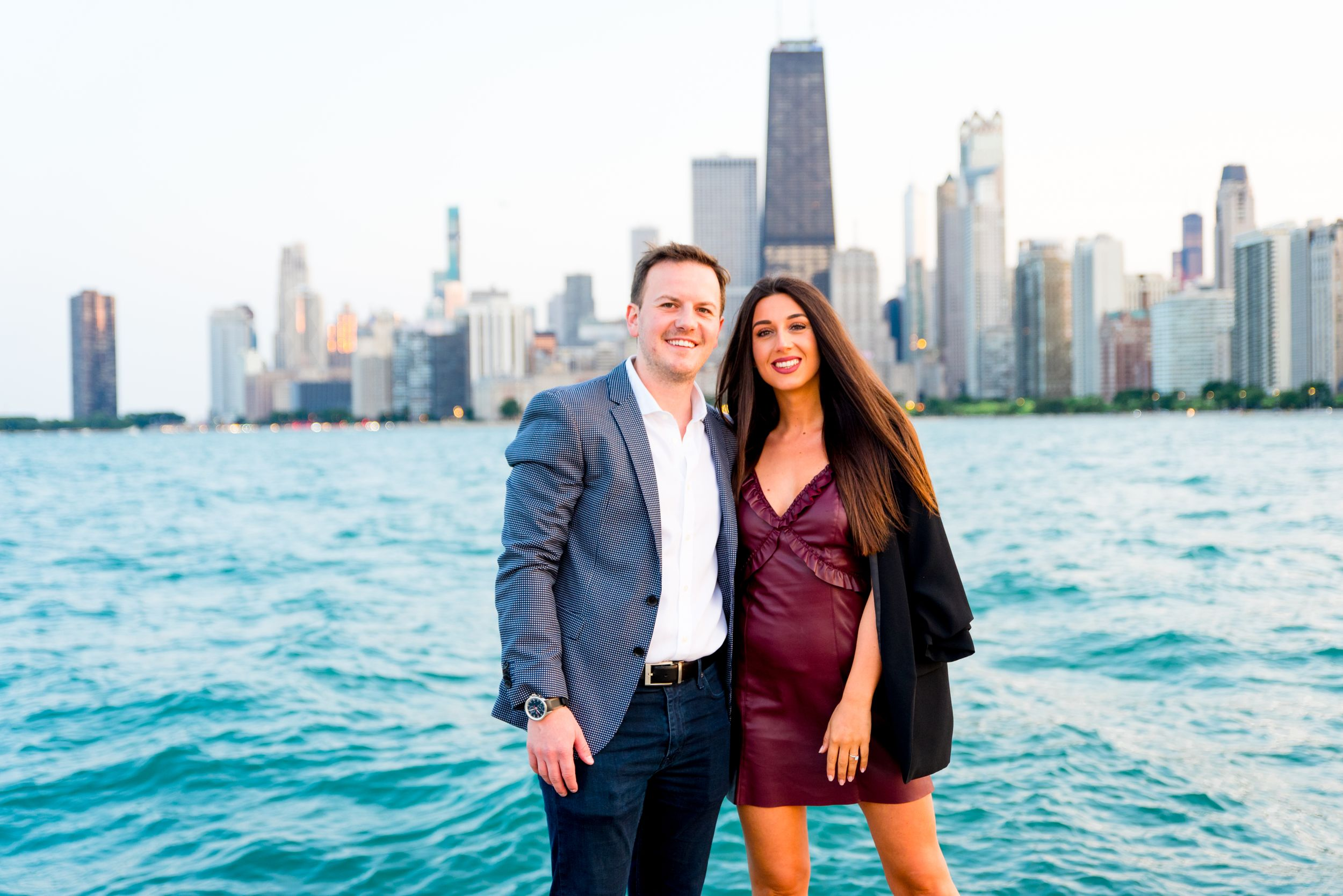 man and woman smiling holding hands in front of Chicago skyline after Chicago proposal