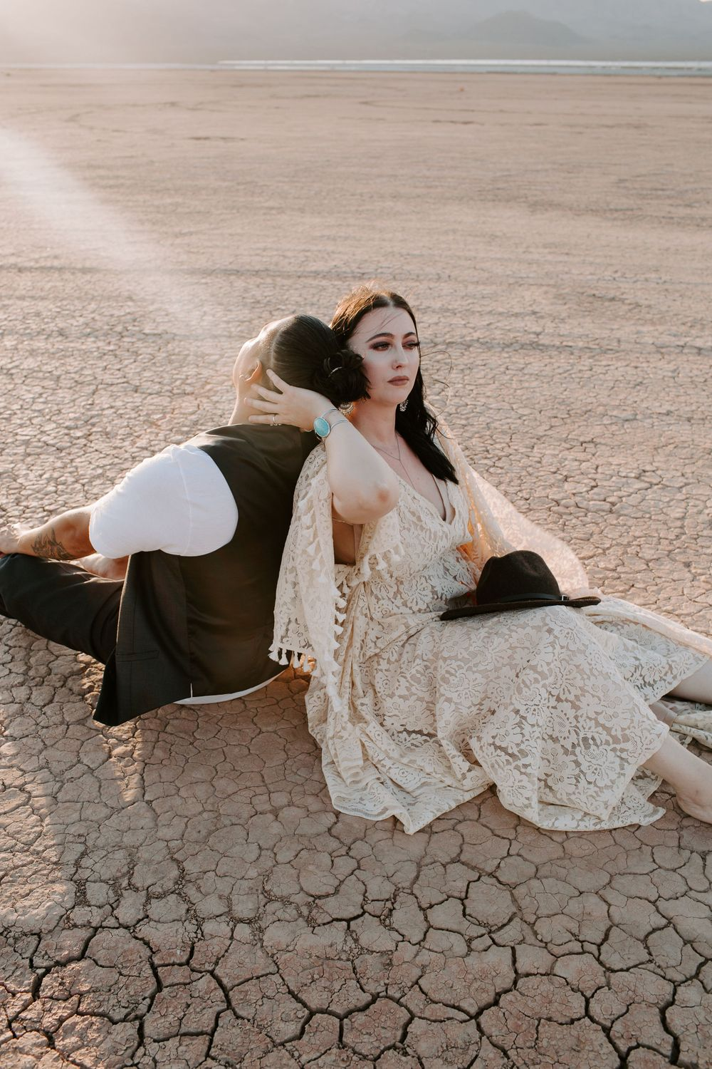 couple sitting on a dry lake bed during their Nevada elopement