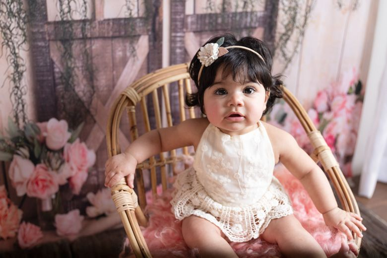 baby girl sitting in a chair in our studio in Lahore