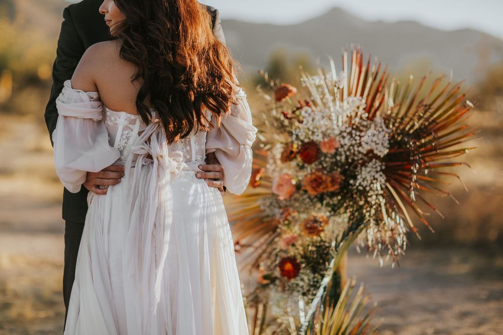rebecca skidgel photography arizona elopement wedding photographer groom holding brides waist bride wearing a daci gown