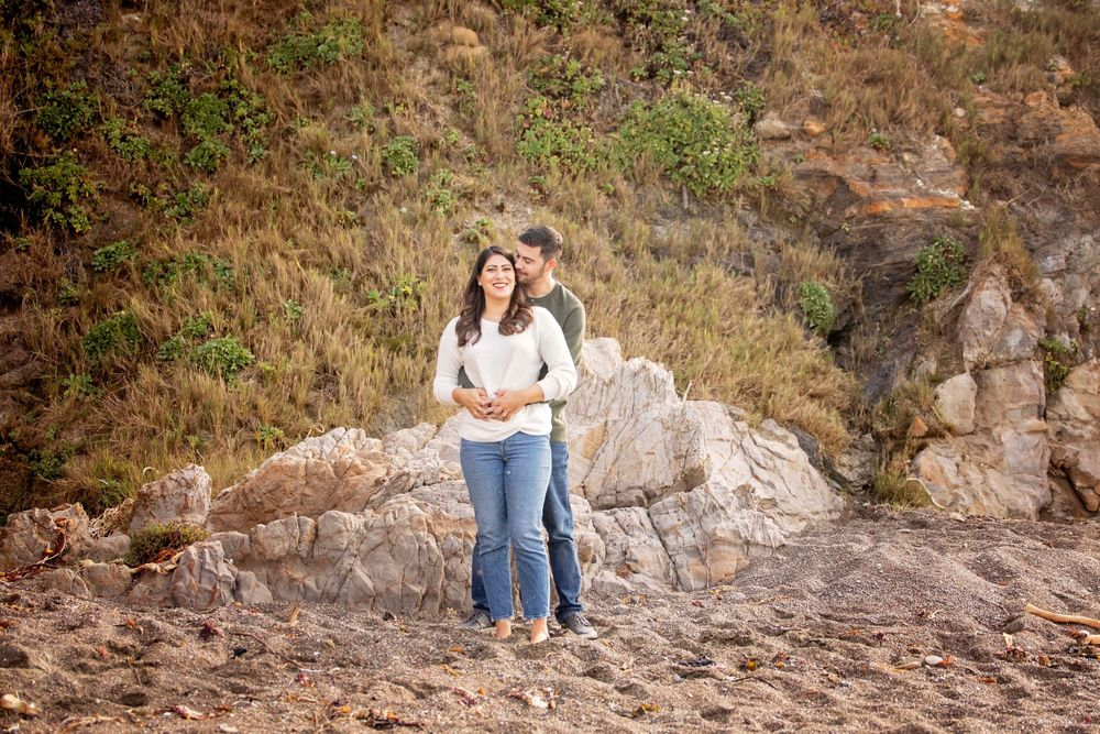 Couple posing for a photo at Moonstone Beach with hillside and rock in the background
