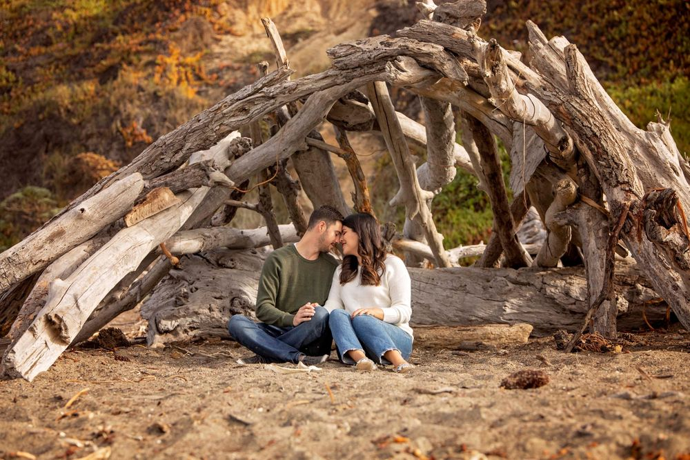 Couple cuddling inside a driftwood structure at Moonstone Beach