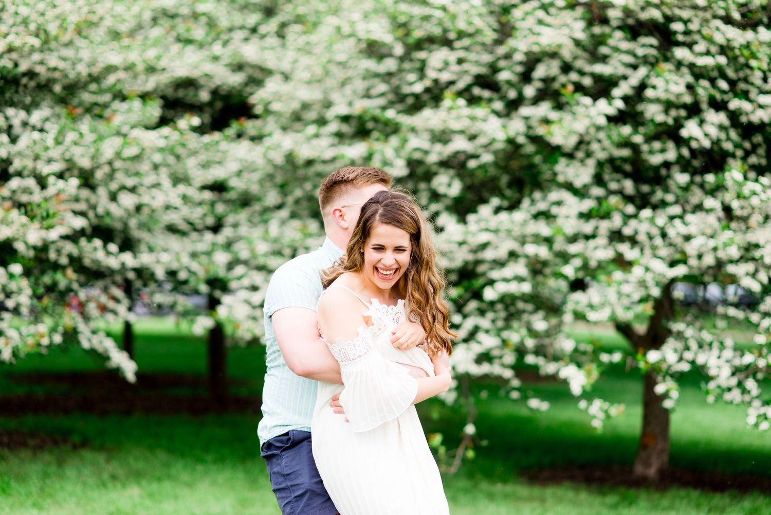 engaged couple playfully hugs and spins around in front of white flower bush at Chicago Montrose Harbor