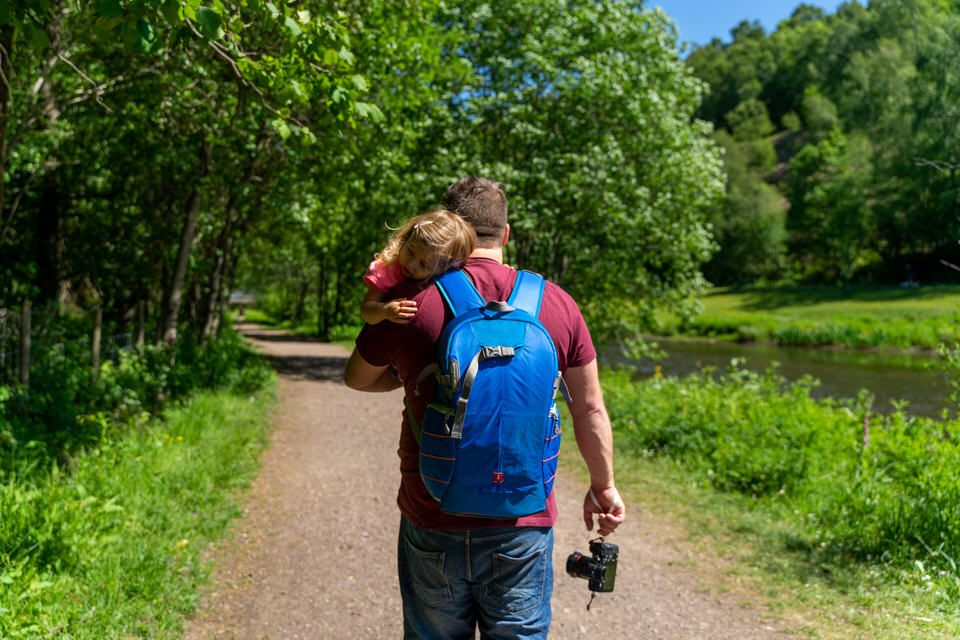 Lloyd Richards Photography carrying his child with camera and backpack