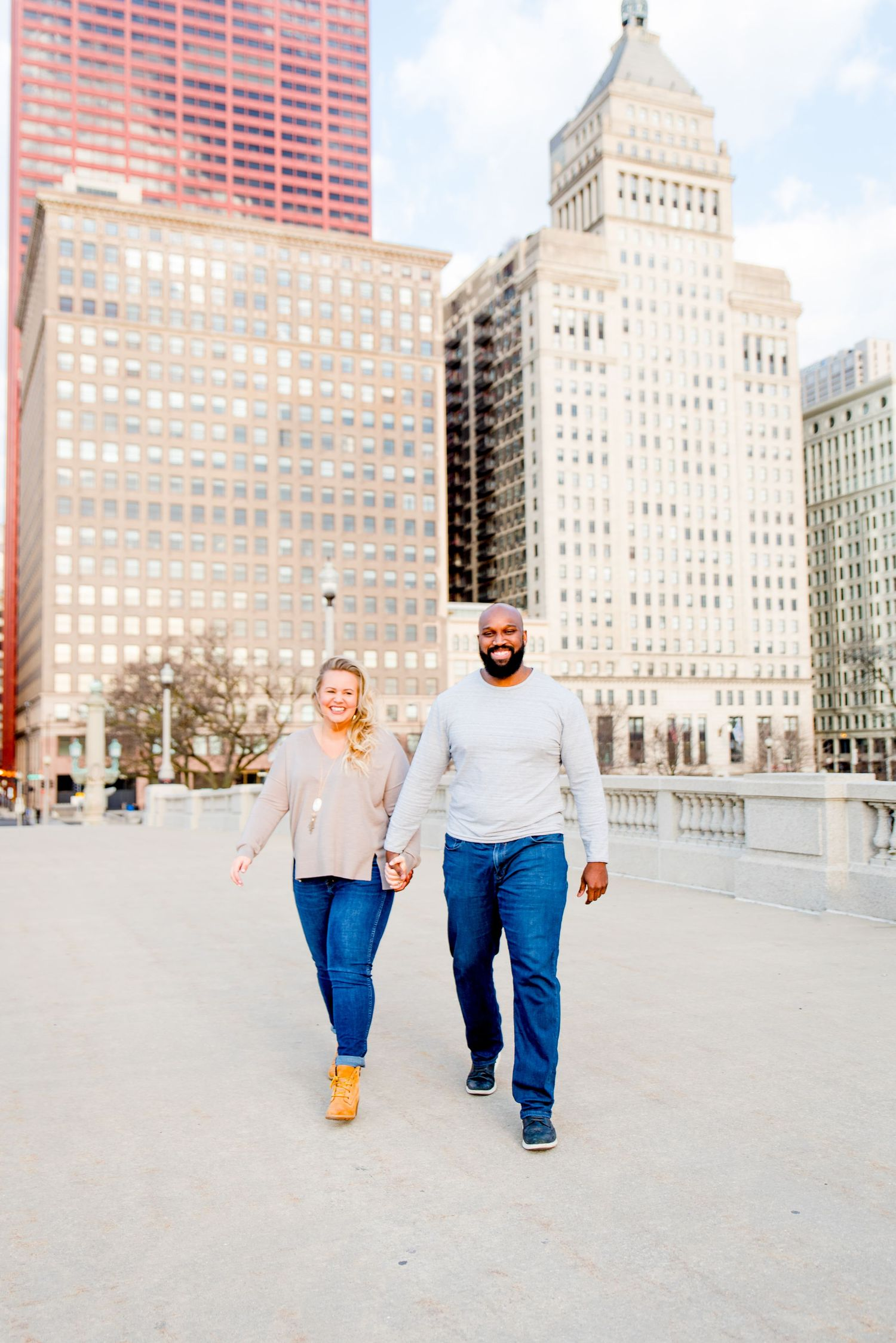 man and woman walking in front of Michigan Ave for Chicago engagement photos