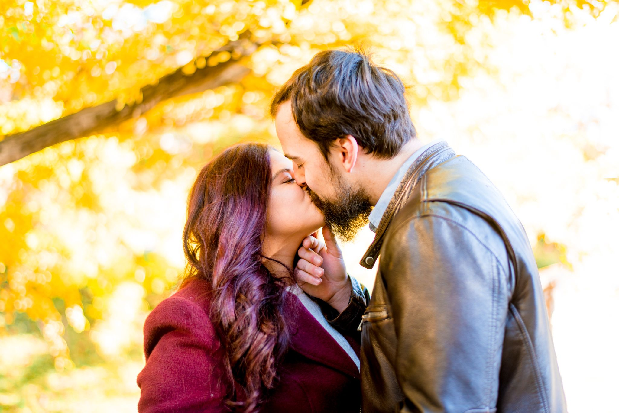brown hair man kissing red hair woman in red coat under yellow trees in Central Park in the fall at sunrise