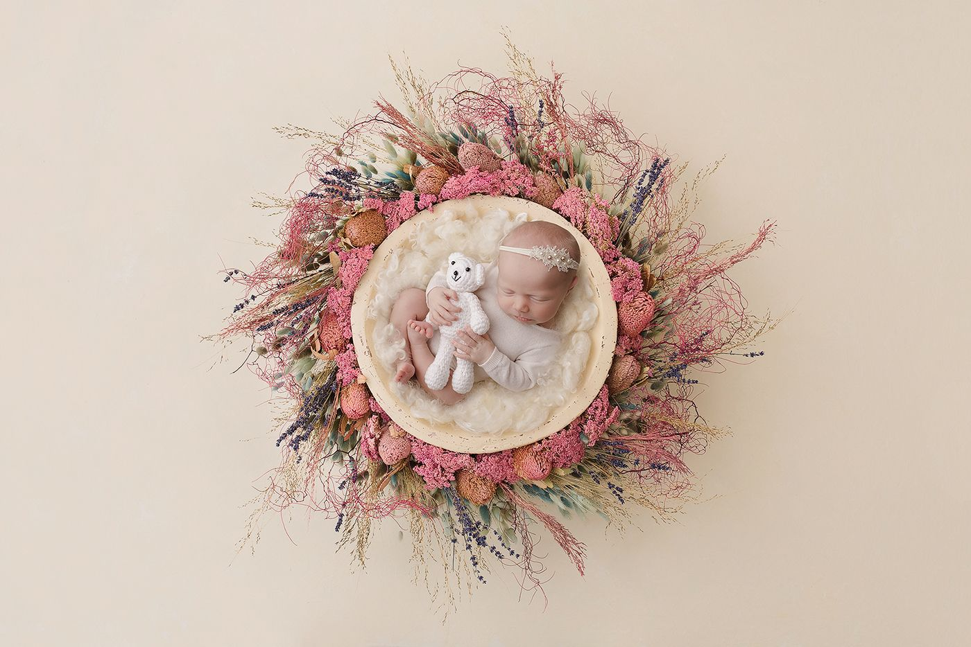 A baby girl in a floral next holding a teddy taken by Little Brown Rabbit Photography in Perth newborn studio