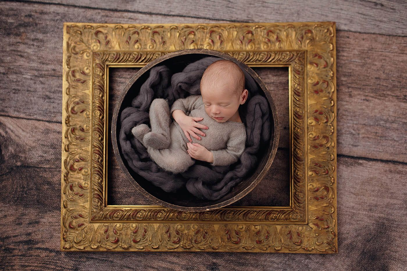 A newborn baby in a bowl surrounded by a gold frame for a newborn photo shoot in Maylands, WA