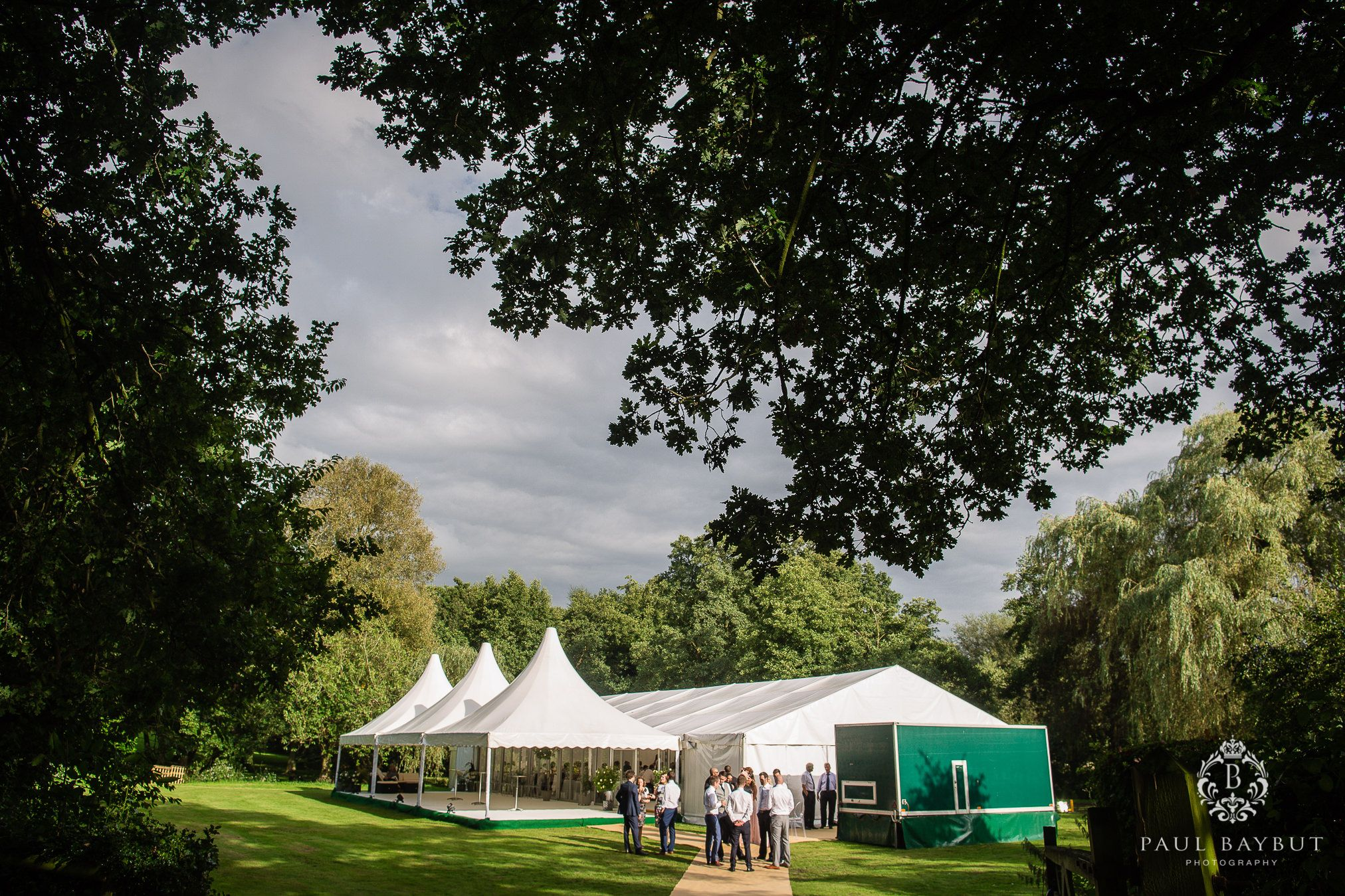 Wedding guests congregate outside a marquee on a summers day at a Cheshire garden wedding