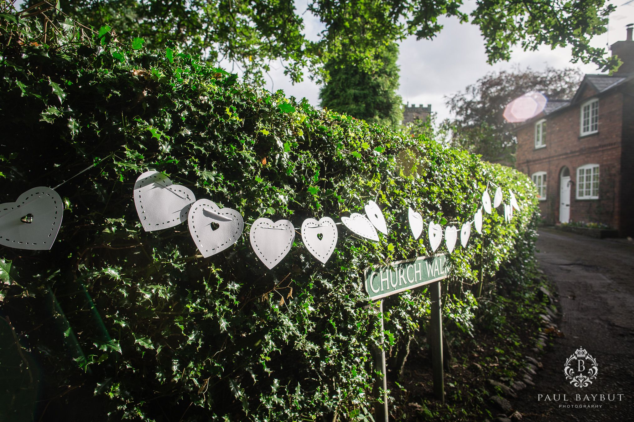 Church Walk in Cheshire with wedding decorations strewn across a garden hedge
