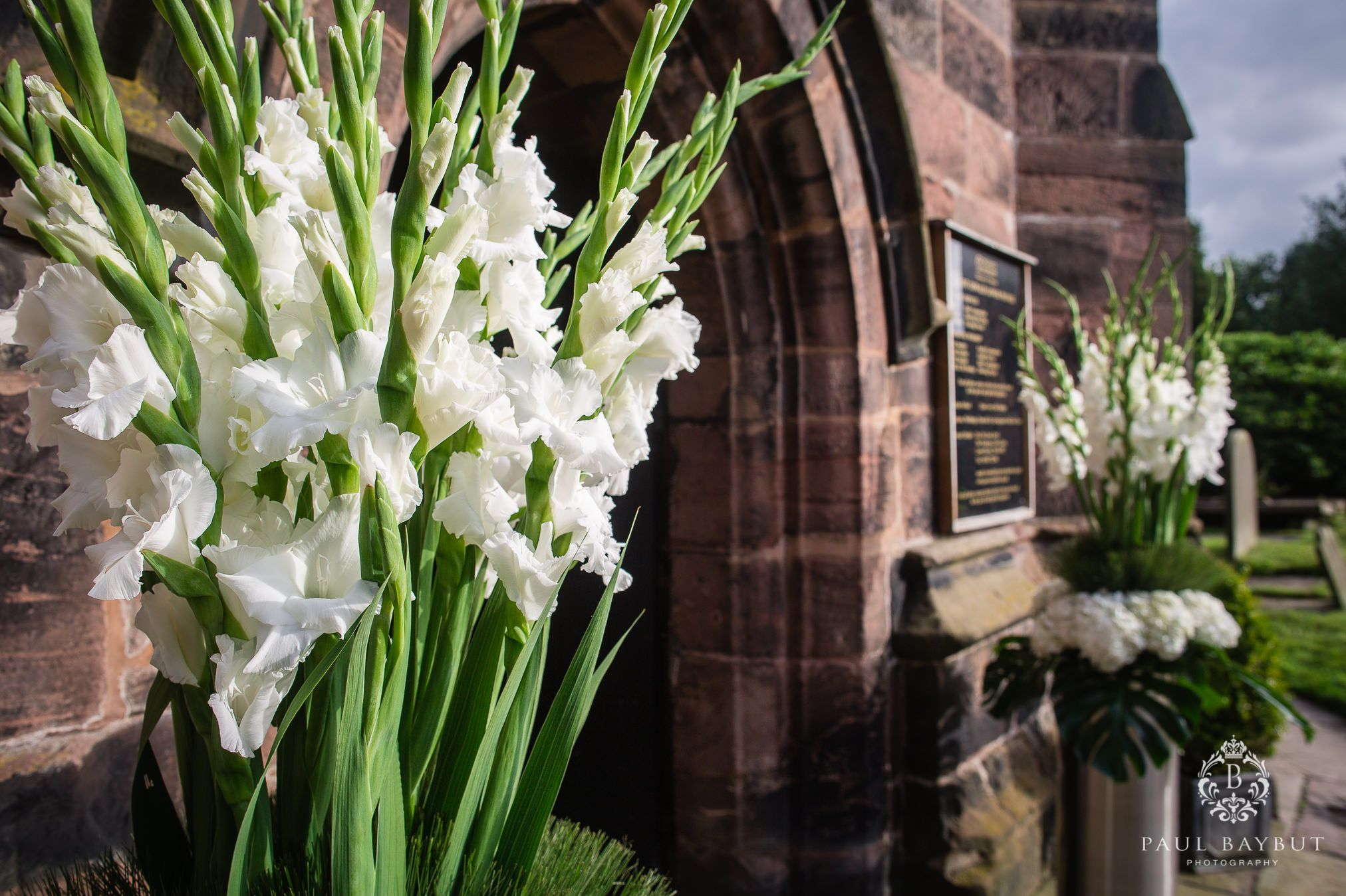 White wedding flowers outside the doors of St Oswald's church in Peover Cheshire on a sunny day