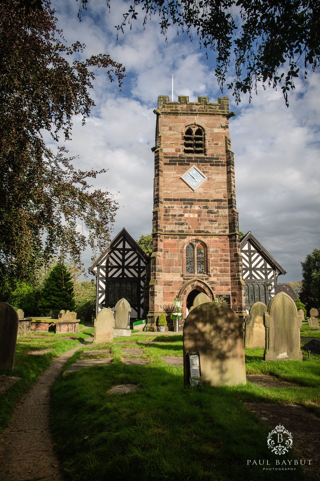 St Oswald's church tower clock and graveyard in Little Peover Cheshire on a sunny day