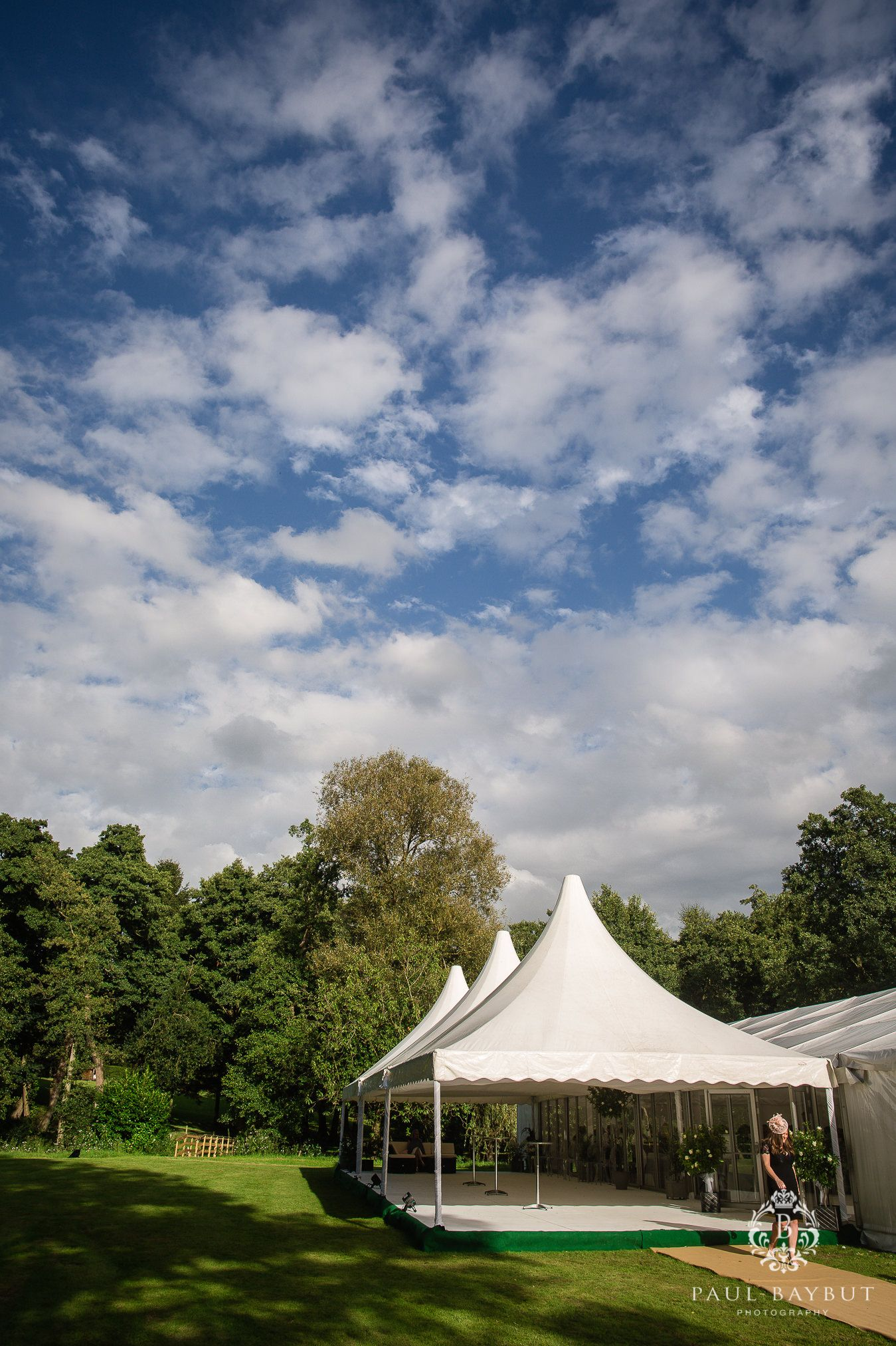 Cheshire wedding marquee venue on a green lawn with sunny blue skies and fluffy white clouds