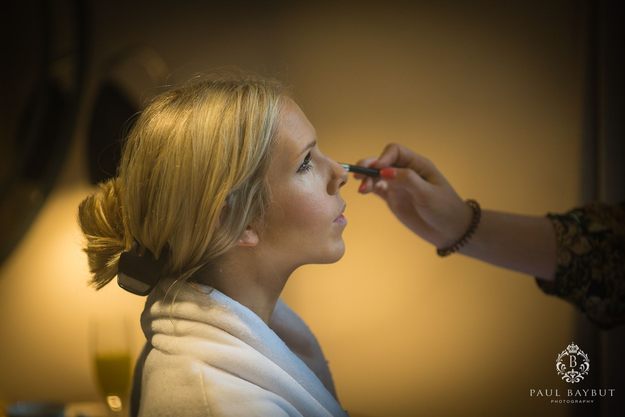 Bride receives bridal make-up preparation in her bedroom