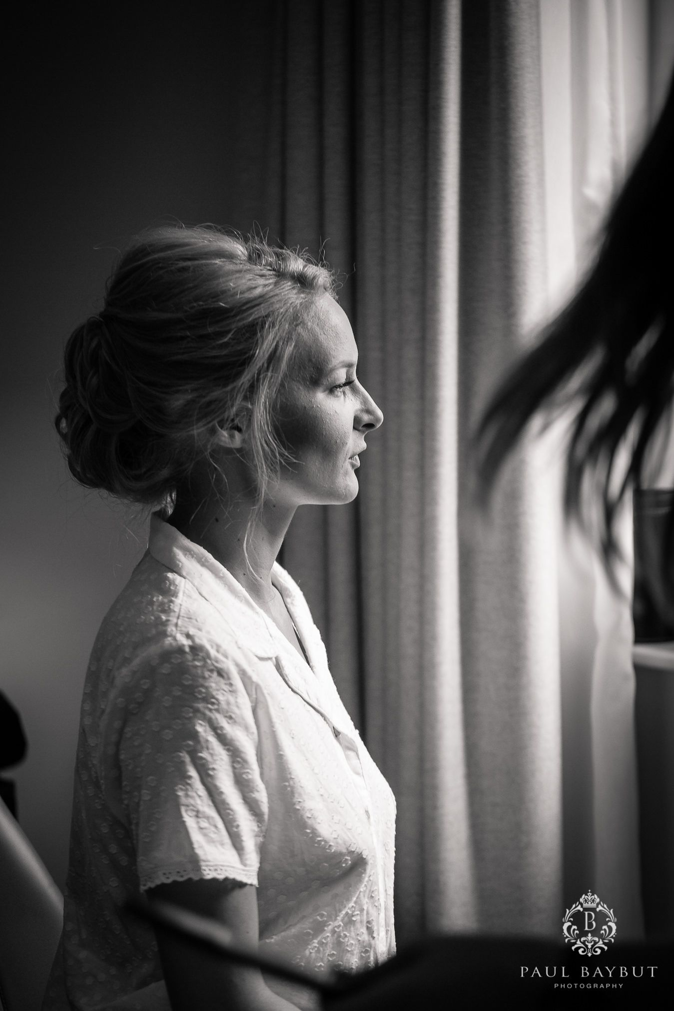 Seated blonde bride is lit by window light awaiting her wedding make up indoors on her Cheshire wedding day