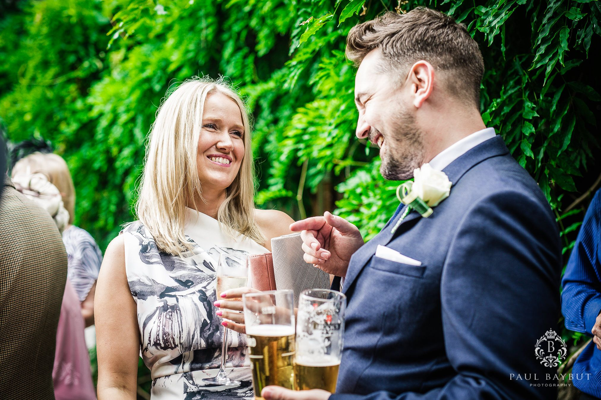 A smiling female and male wedding guest chat together at an outdoor Cheshire wedding