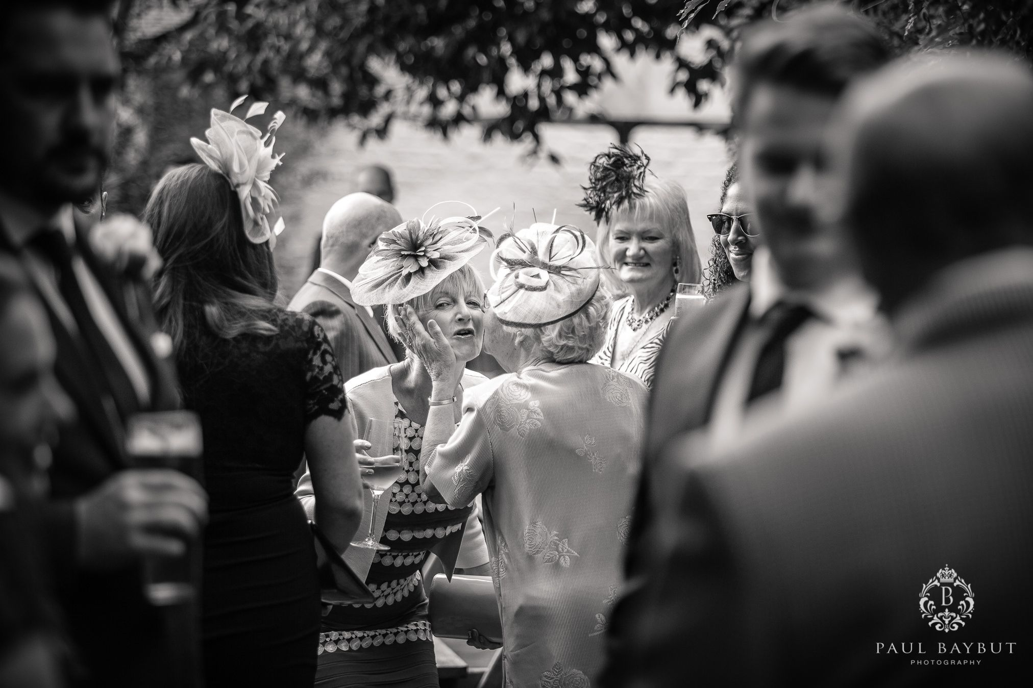 Mother of the bride recieves a big kiss from a female relative among wedding guests at a Cheshire marquee wedding