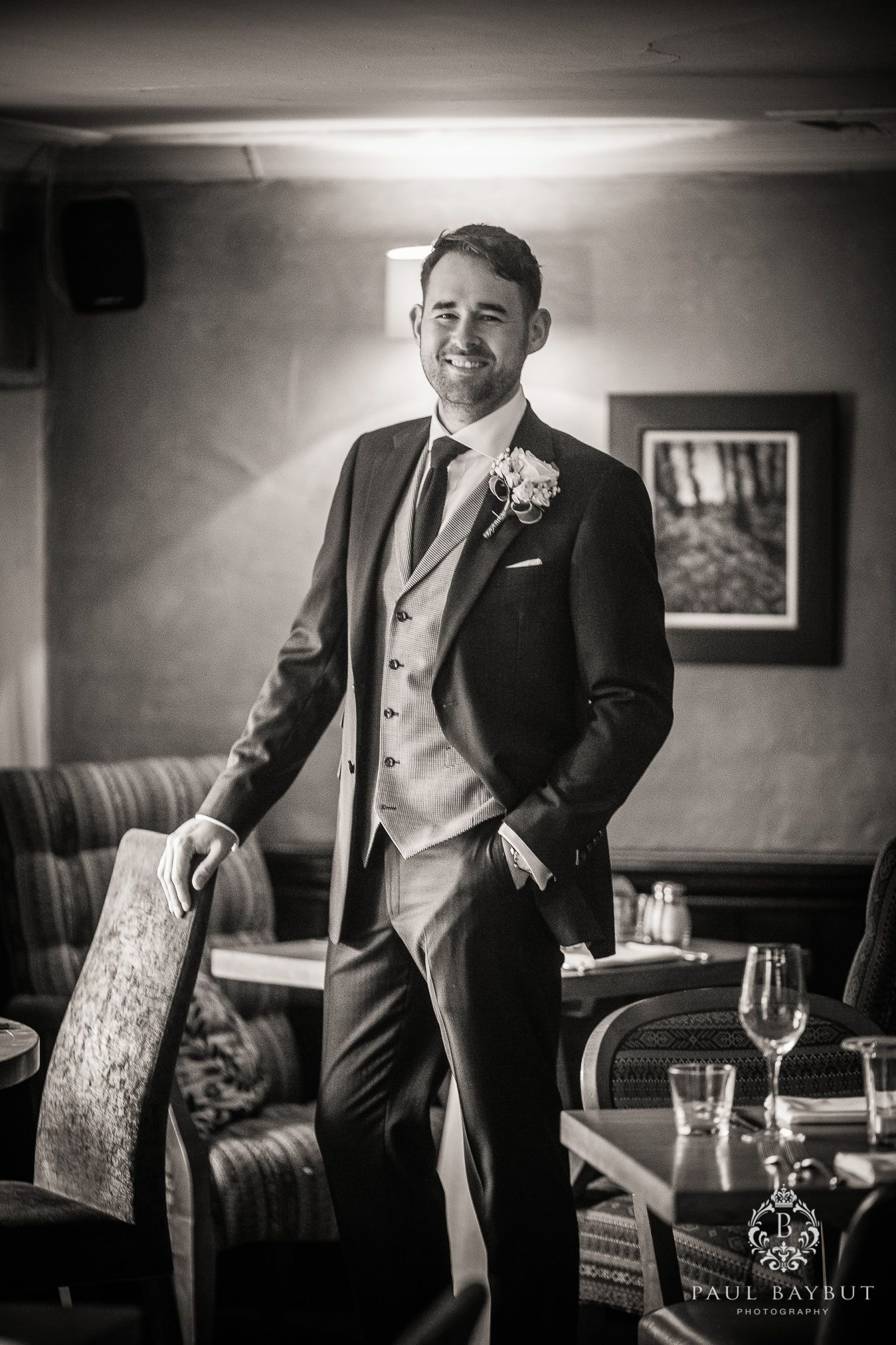 Proud smiling groom stands in his local Cheshire pub with his hand in his pocket on the morning of his wedding day
