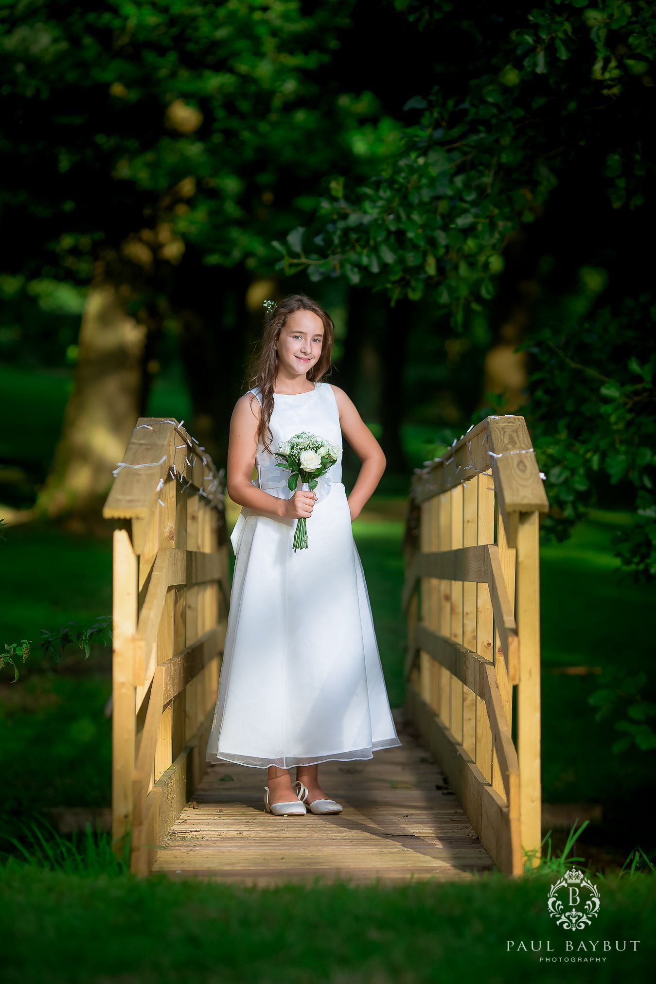 Young flower girl in white dress holding white flowers stood on a wooden bridge in the garden at a Cheshire wedding