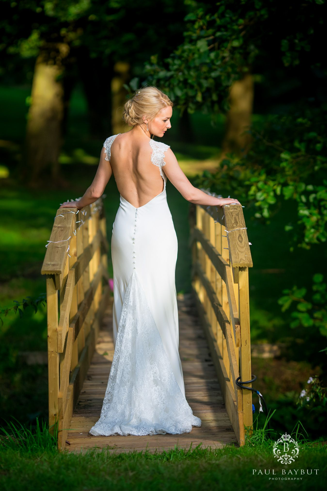 Bride wearing white wedding dress standing on a wooden bridge in a Cheshire garden
