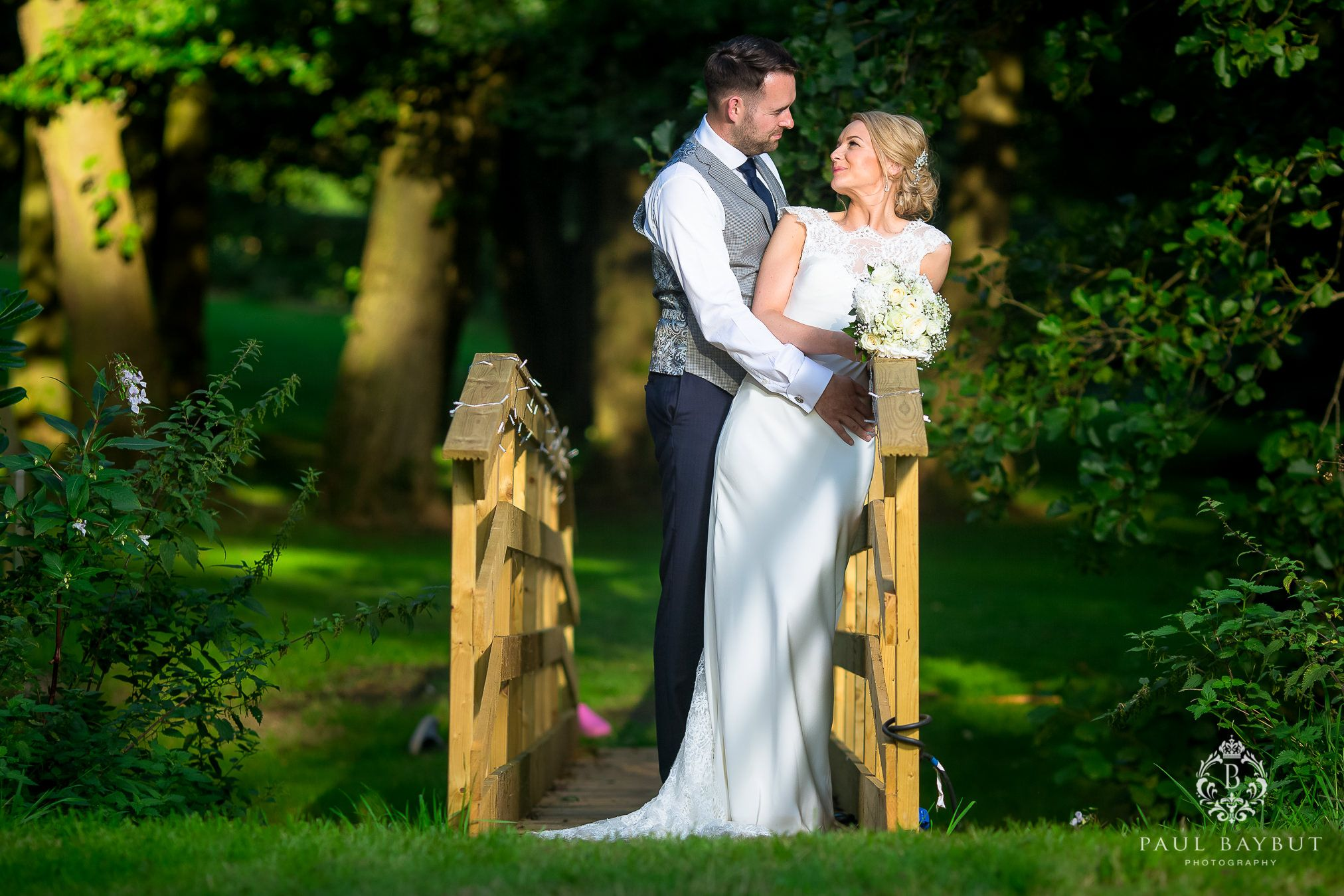 Bride and groom standing on a wooden bridge in the garden of their Cheshire marquee wedding
