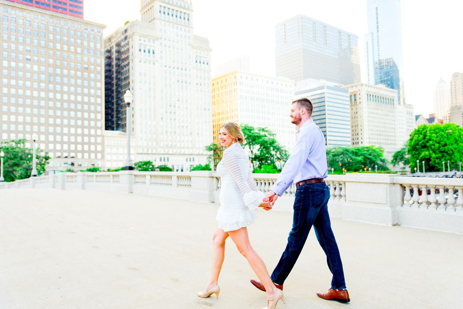 woman in white dress leading man in jeans and blue dress shirt through downtown Chicago