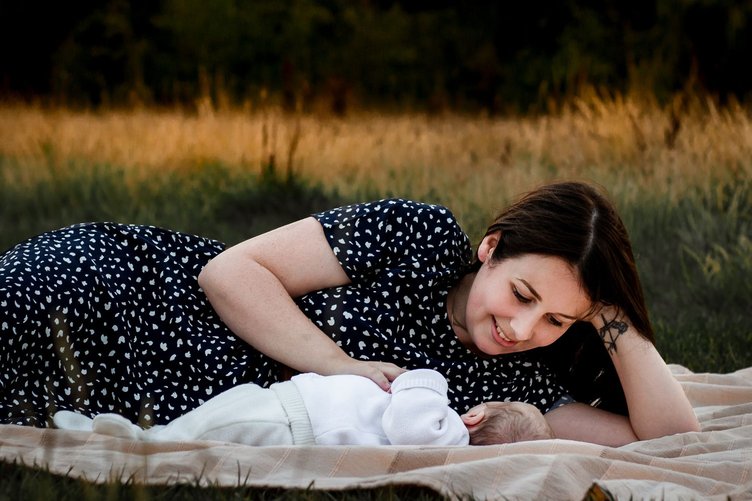 In a field in Havant a new Mum lays beside her newborn Son smiling.