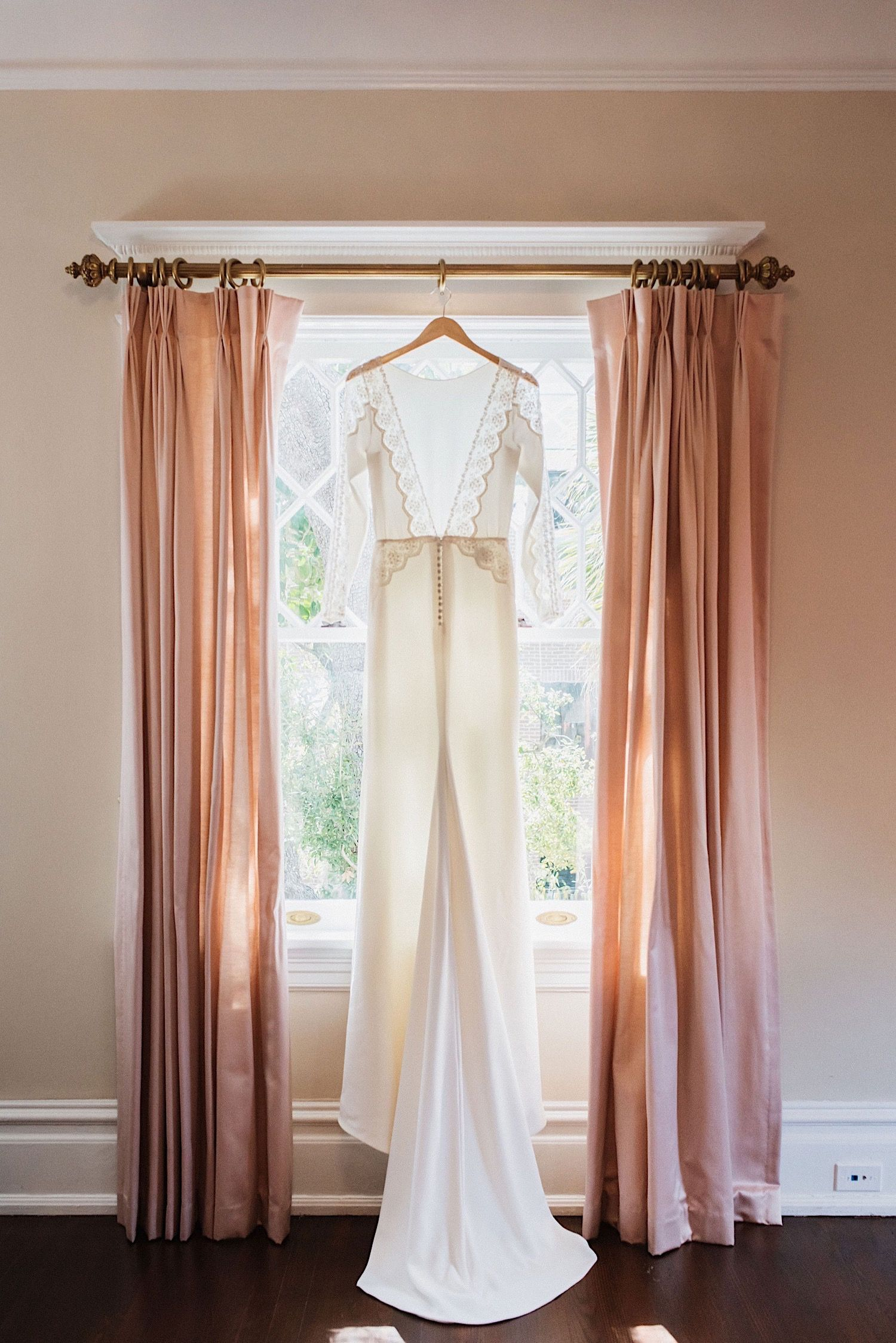 Wedding dress hanging in the window with pink curtains at the Orlo , a wedding venue in Tampa, FLorida