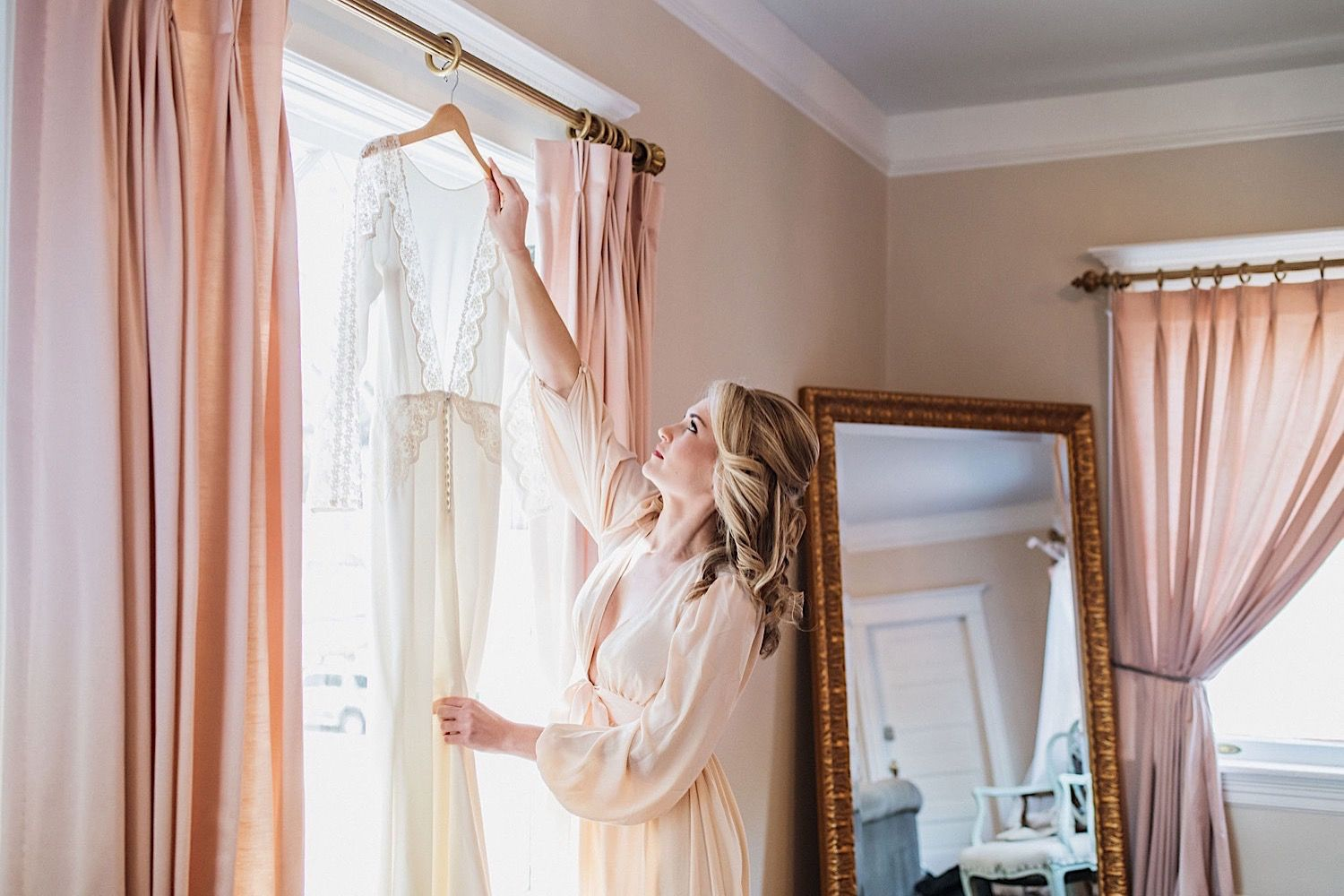Bride in a silk robe reaching for her wedding dress