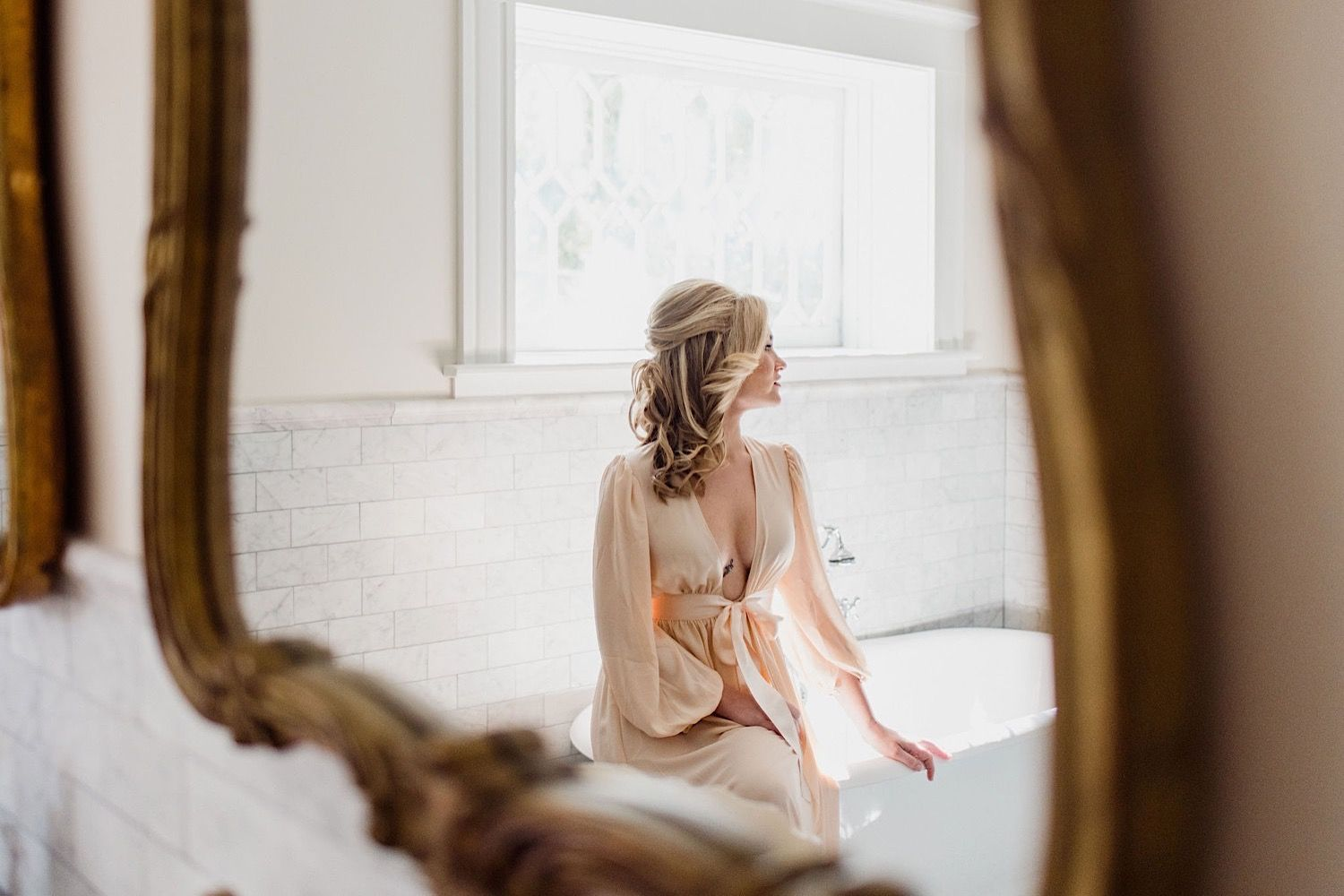 Bride in a silk robe sitting on a clawfoot bathtub in the mirror