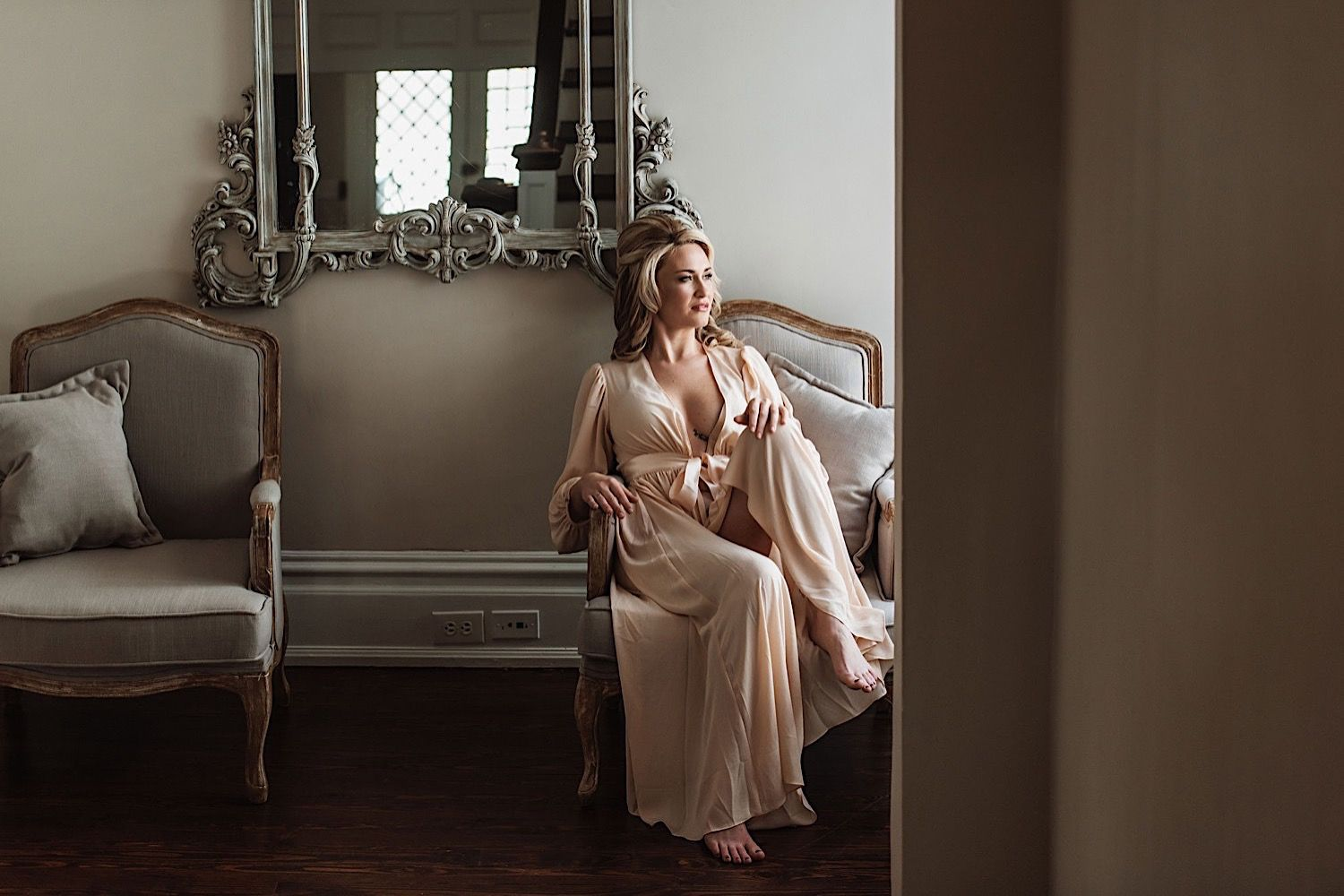 Bride sitting on a love seat in peach silk robe and looking out the window