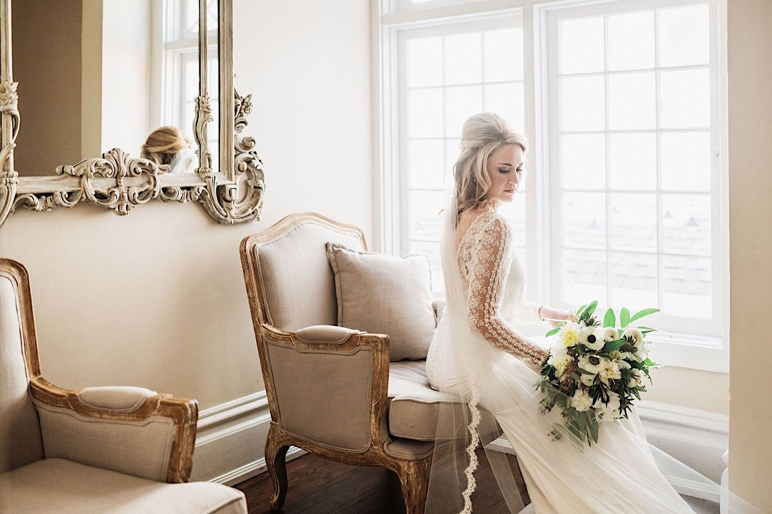 Bride in wedding dress with bouquet sitting on  chair in front of the window at The Orlo